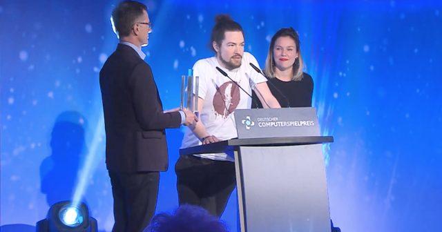 Deutscher Computerspielpreis 2017: Dominik Abé von Mimimi Productions (Mitte) mit den Laudatoren Jens Kosche (Electronic Arts) und Mareike Ottrand (Studio Fizbin)