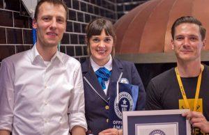 Stefan Marcinek (CEO Assemble Entertainment) und Nikolay Abrosov (General Manager Pizza.de) erhalten von der Guinness-Preisrichterin die Käsepizza-Weltrekord-Urkunde.