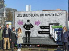 """Die HAW-Studenten präsentieren ihr """"Life is Strange""""-Plakat mit Square-Enix-Produktmanager Nils Blankenstein (3. von links) und Marketing Director Lars Winkler (rechts)"""
