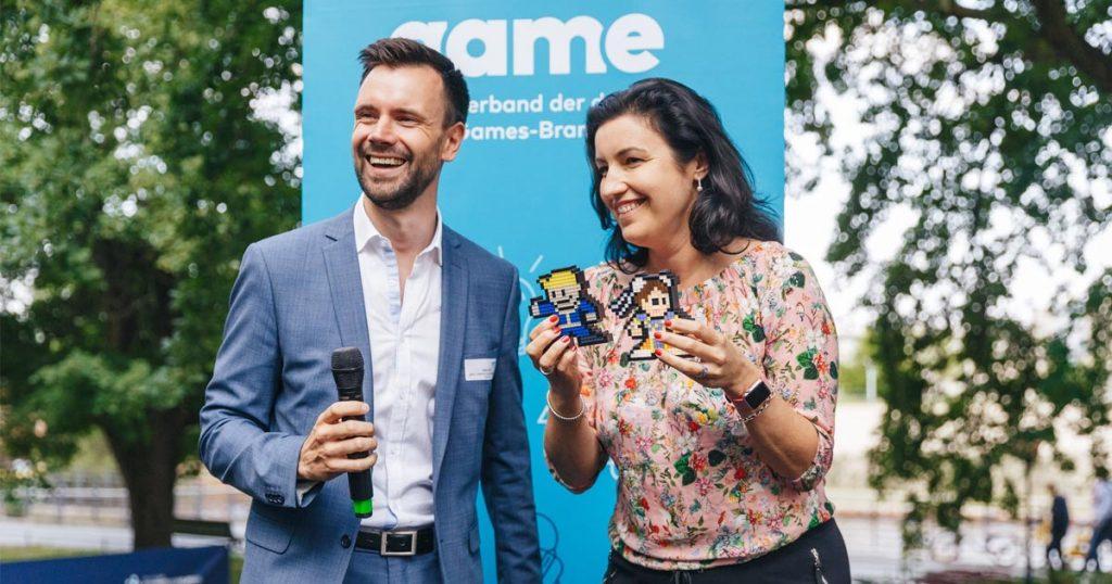 Game-Sommerfest 2018: Geschäftsführer Felix Falk bedankt sich bei Digitalstaatsministerin Dorothee Bär (CSU) mit zwei Videospiel-Figuren, die einen Platz im Kanzleramt finden sollen (Foto: Game-Verband / Jakob Nawka)