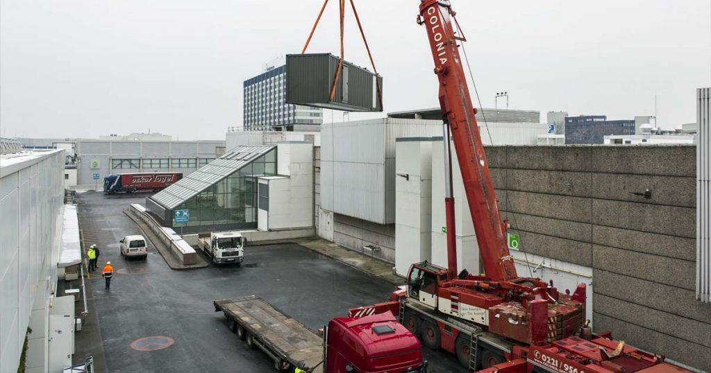 Ein Schwerlastkran hievt ein neues Notstromaggregat auf das Dach der Halle 10 (Foto: KoelnMesse / Ludolf Dahmen)