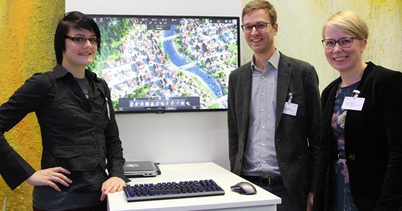 """Digitalgipfel 2018: Sabrina Auer (Ubisoft Blue Byte), Sebastian Broch und Maren Schulz (beide Game-Verband) zeigen """"ANNO 1800"""" (Foto: GamesWirtschaft)"""