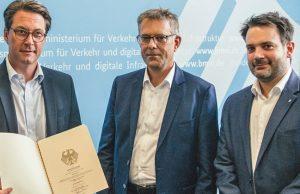 Verkehrsminister Andreas Scheuer (CSU) überreicht den Förderbescheid an die KoelnMesse-Manager Georg Klumpe und Gert Messerschmidt (Foto: KoelnMesse)