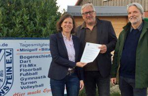 Staatssekretärin Kristina Herbst (CDU) übergibt den eSport-Förderbescheid an Helge Kühl (TSV Neudorf-Bornstein - rechts: Bürgermeister Holger Bohrmann) - Foto: Innenministerium SH